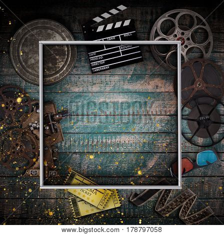 Cinema concept of vintage film reels, clapperboard and other tools on old wooden background.