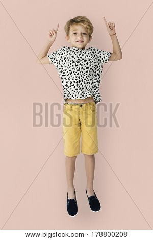 Young blonde boy jumping mid-air portrait