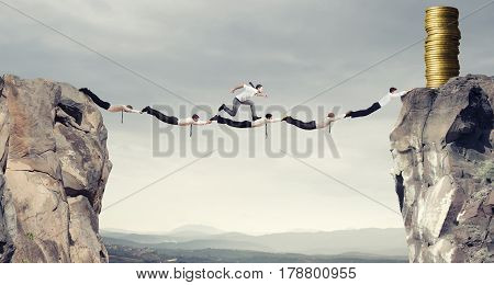 Businessmen working together to form a bridge between two mountains to get the money