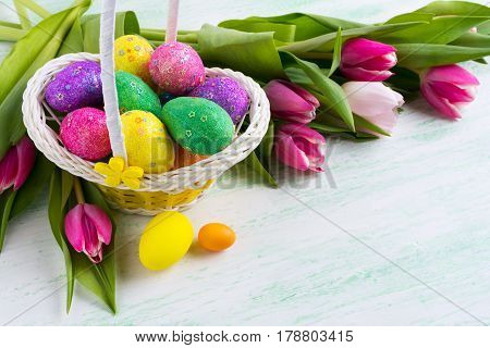 Easter Multicolored Glitter Eggs In Yellow Basket And Red Tulips Background