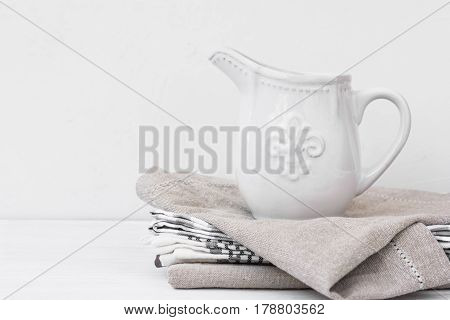 White vintage pitcher on a stack of linen towels styled image with copyspace for product marketing social media banner header template
