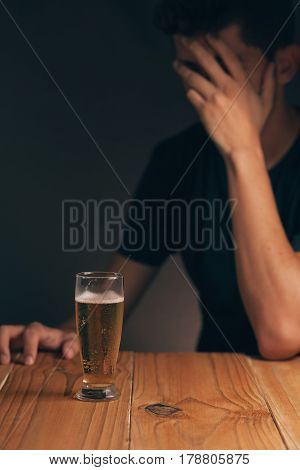Concept Of Alcoholism. Sad Man At The Table With A Glass Of Beer In A Dark Room.