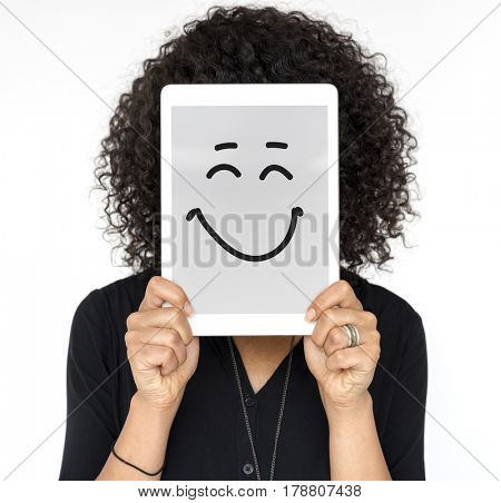 Woman holding tablet covering her face with smiley