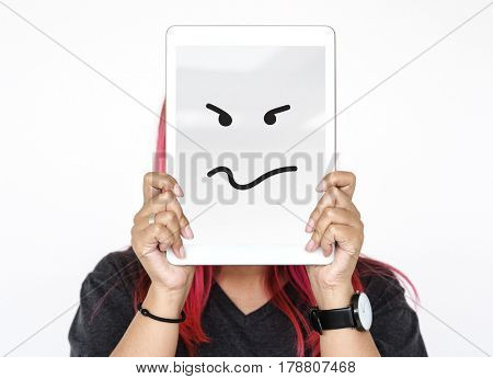 Woman holding tablet covering her face with angry unhappy