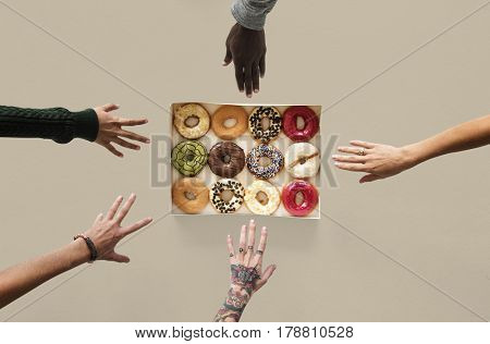 Group of hands reaching sweeten donut dessert