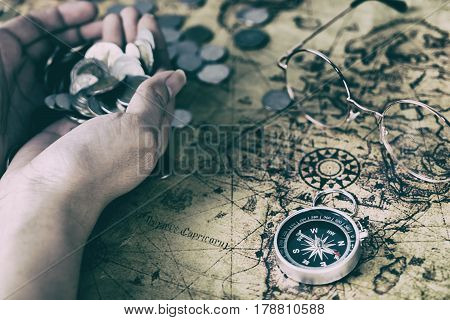 Treasure hunter map with hand full of coin