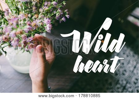 Life quote. Motivation quote on soft background. The hand touching purple flowers. Wild heart.