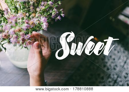 Life quote. Motivation quote on soft background. The hand touching purple flowers. Sweet.
