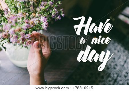 Life quote. Motivation quote on soft background. The hand touching purple flowers. Have a nice day.
