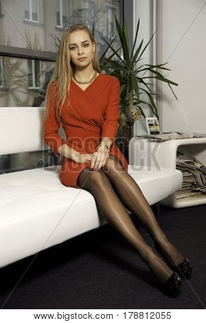 Portrait of a beauty young adult attractive pretty blond girl on a sofa