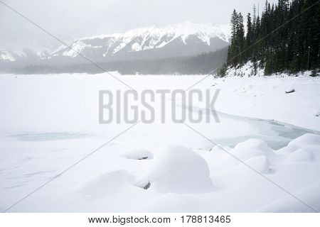 Winter Kananaskis Lake Landscape with snowy rock formation in the foreground.