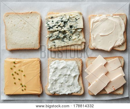 Different kinds of cheeses on toasts on paper close up