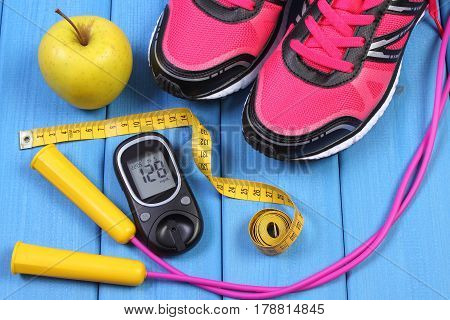 Glucometer, Sport Shoes, Fresh Apple And Accessories For Fitness On Blue Boards
