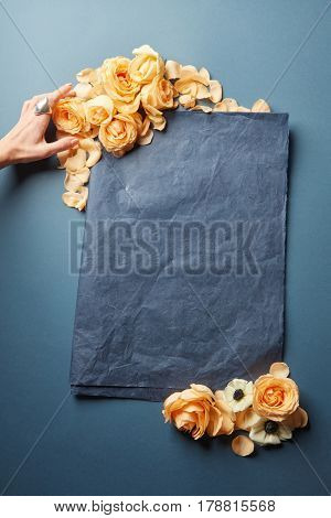 Female hand decorating blank sheet of paper with flowers. Empty frame for text