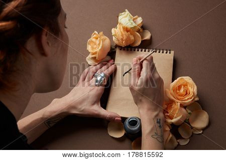 Woman with brush writing on paper with roses buds