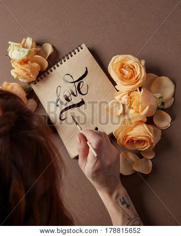 Woman with brush writing love word on craft paper