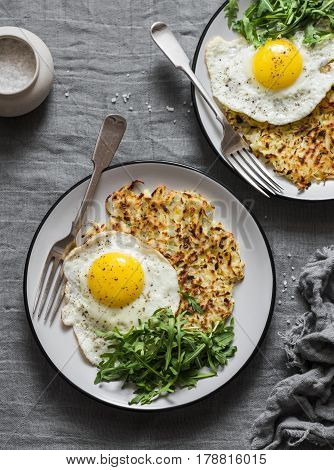 Hash Browns fried egg and arugula on grey background top view. Delicious simple lunch