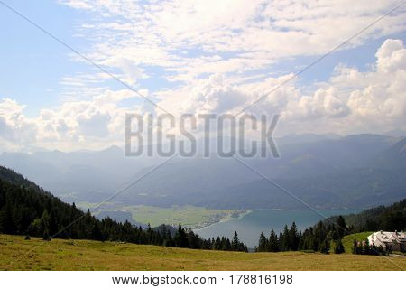Travel To Sankt-wolfgang, Austria. The View On The Green Forest And A Meadow With A Lake And The Mou