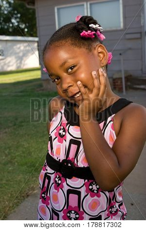 Happy African American little girl smiliing outside.