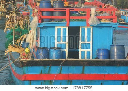 Fishing boat close-up of cabin, deck and equipment at back of boat and roof.  Colorful blue boat with red, white and black trim.  Fishing is an important industry in Vietnam Asia.  The harbor is a popular tourist site. Horizontal. No people. Photography.