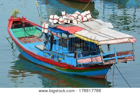 Fishing boat colorful close-up. Moored boat with reflection in water. Fishing is an important industry in Vietnam Asia.  The harbor is a popular tourist site. Horizontal. No people. Photography.