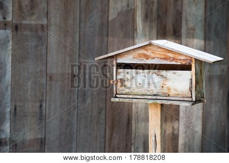 close up of old wooden mailbox with wood background
