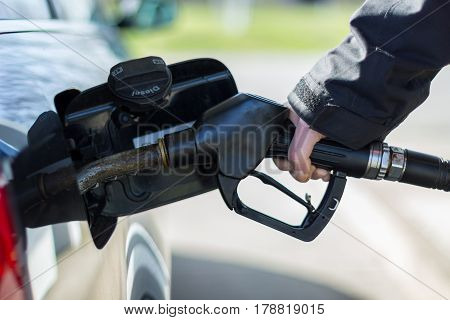 a hand on a gas pump nozzle