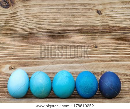Colorful blue  Easter eggs on wooden background.