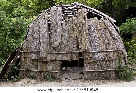 Plimoth Plantation, Plymouth, Massachusetts - September 10, 2014 - Close view of a Wampanoag Indian hut made of branches and partly covered in bark in the Wampanoag Indian Village at Plimoth Plantation, Plymouth, Massachusetts surrounded by trees and foli