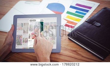 Composite image of flower image on website against over shoulder view of hipster woman using tablet