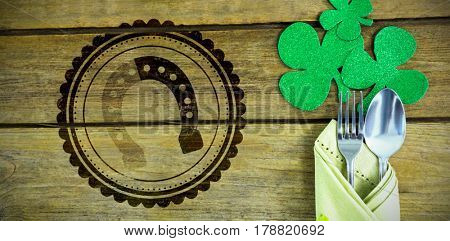 Composite image of St Patrick Day horseshoe symbol against st patricks day fork and spoon wrapped in napkin with shamrocks