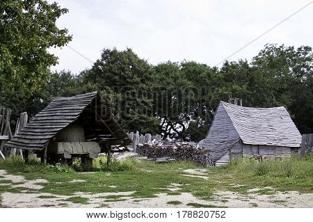 Plimoth Plantation, Plymouth, Massachusetts - September 10, 2014 - Wide view of a Pilgrims kiln covered by an old planked roof and old gray wood shed in the Pilgrim Village at Plimoth Plantation, Plymouth, Massachusetts surrounded by trees and foliage