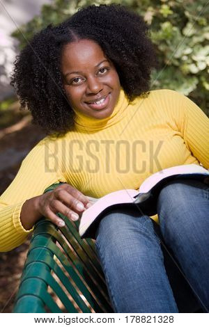 African American woman reading outside at a park.