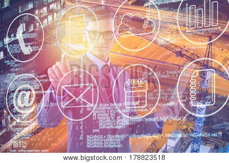 Businessman holding glass sheet and touching invisible screen against high angle view of glowing road 3d