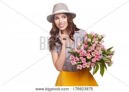 Beautiful girl in hat with flowers tulips in hands on a light background