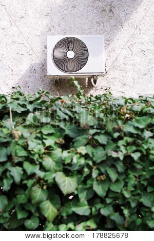 vertical front view of a white air conditioning unit behind a wall of green leaves