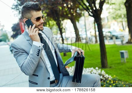 Portrait of young elegant businessman talking on smartphone on city street holding suitcase.