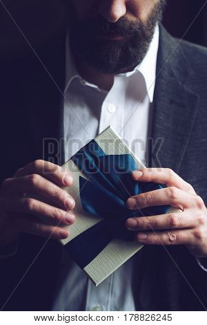 Horizontal close up of Caucasian man with beard in black suit and white shirt holding a gift box with blue large ribbon natural light