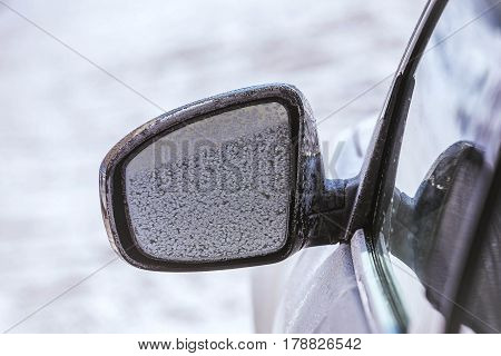 Car wing mirror with snow in the winter