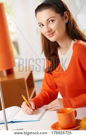 Student girl sitting at desk at home studying writing to workbook, looking at camera smiling.