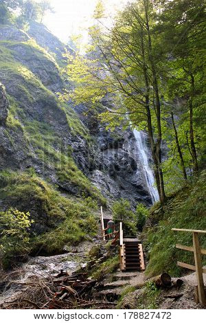 Travel To Sankt-wolfgang, Austria. The Waterfall In The Mountains Green Forest.