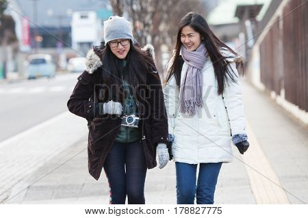 Two women backpacker talk and smile togeter while travel in nikkoJapan