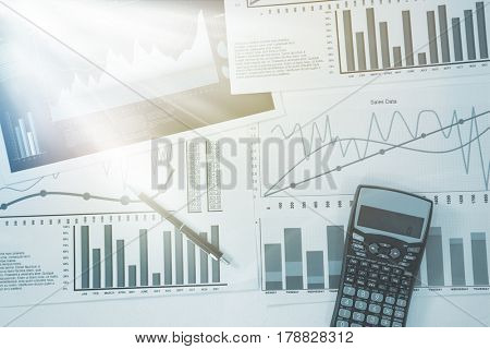 High angle view of graph sheets with pen and calculator