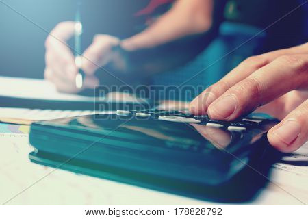 Calculator With Woman Hand Typing And Writing Make Note And Doing Finance.