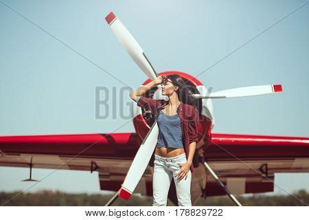 Pilot woman next to propeller plane outdoors in sunny day. Attractive young multi-racial Asian Caucasian sexy girl in jeans shirt and sunglasses standing at sport airplane in airport.