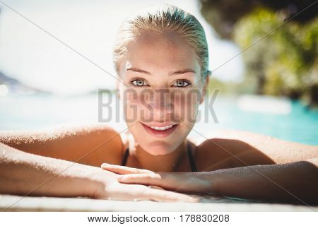 Portrait of beautiful blonde in the pool leaning on the edge