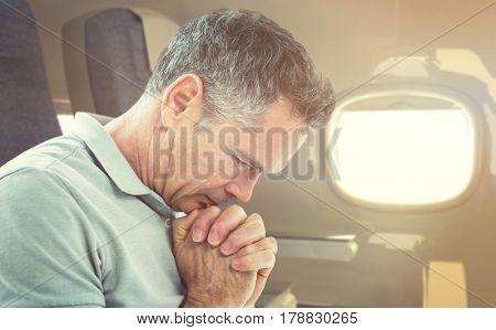 Tensed man standing against window against empty seat in modern plane