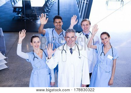 Portrait of medical team standing with their hand raised in hospital