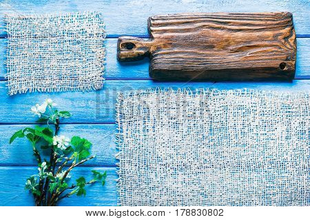 Background of narrow wood planks painted in blue. Bunch of blooming apple tree and young black current twigs. Wood cutting board as title bar