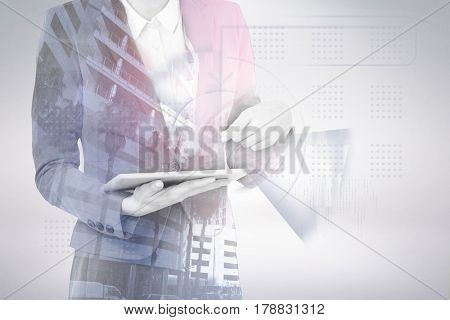 Midsection of businesswoman using digital tablet against buildings in city 3d
